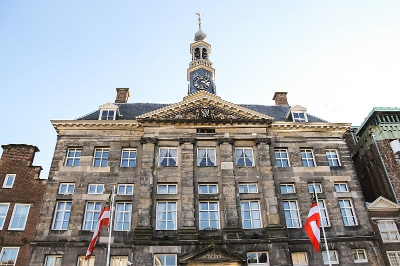 a stately building with a clock tower and two white-red flags in front, the Old Town Hall in Den Bosch