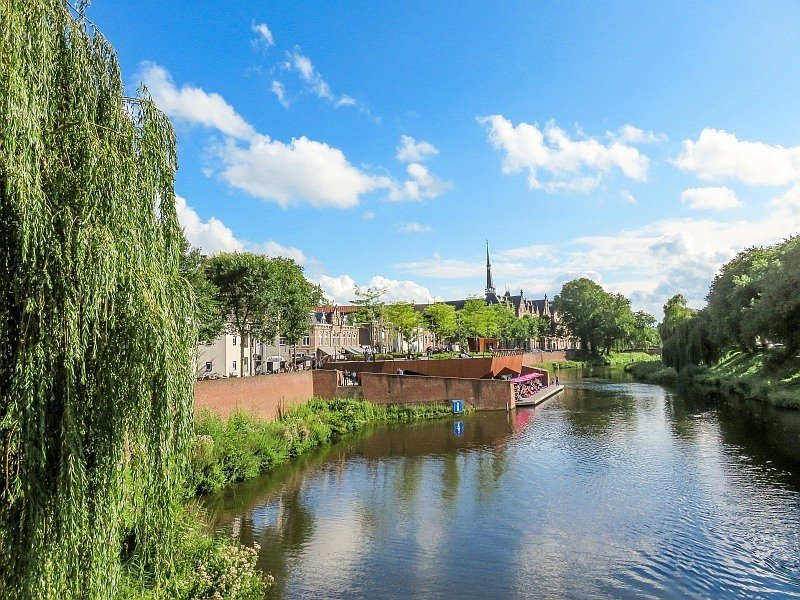 a river as seen from a bridge with a weeping willow on the left and church spire at the background , in the middle a cafe with lots of tables at the river bank on a platform, De Dommel River, Den Bosch
