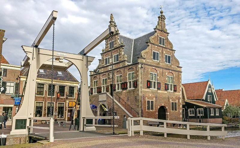 a draw bridge in the front with beautiful buildings with shutters behind against a blue sky with white clouds, De Rijp in the Netherlands