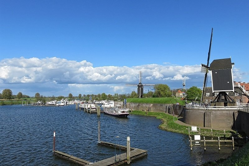 two windmills on the bank of a river harbour with some boats and yachts, Heusden in the Netherlands