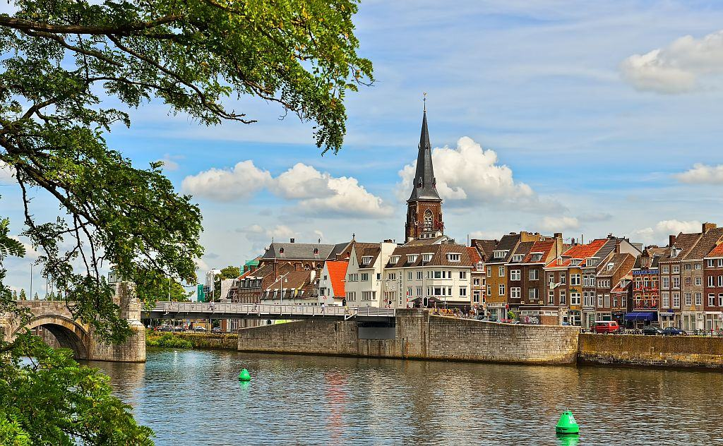 city riverfront with a tower, and old bridge and some green trees at the foreground, Maastricht in the Netherlands