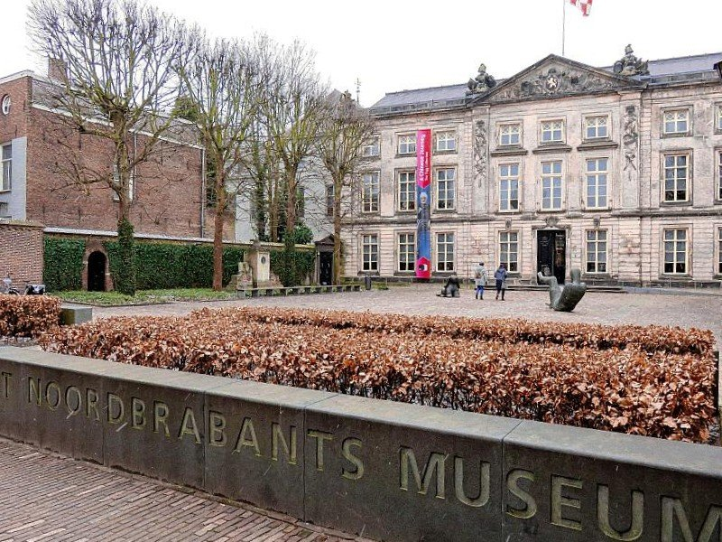 a large building with some sculptures and people in front with a sign: Noordbrabants Museum, Den Bosch