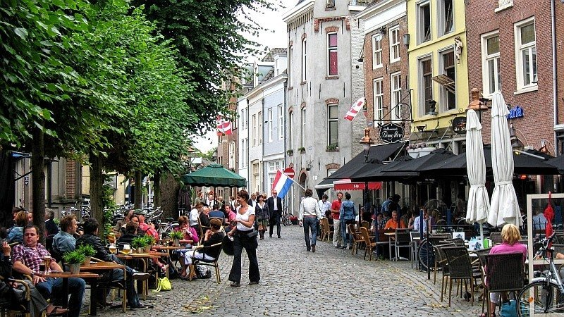 a cobbled stone street with restaurants on both sides and people sitting at the tables, Den Bosch in the Netherlands