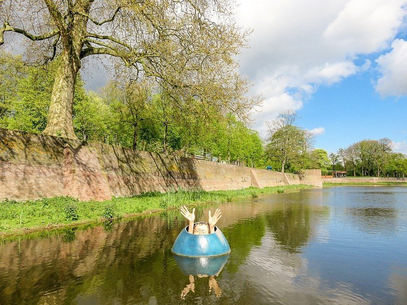 a sculpture of a man coming through an egg with the hands up, like waving for help in the water with old city wall behind and green trees, Den Bosch, the Netherlands