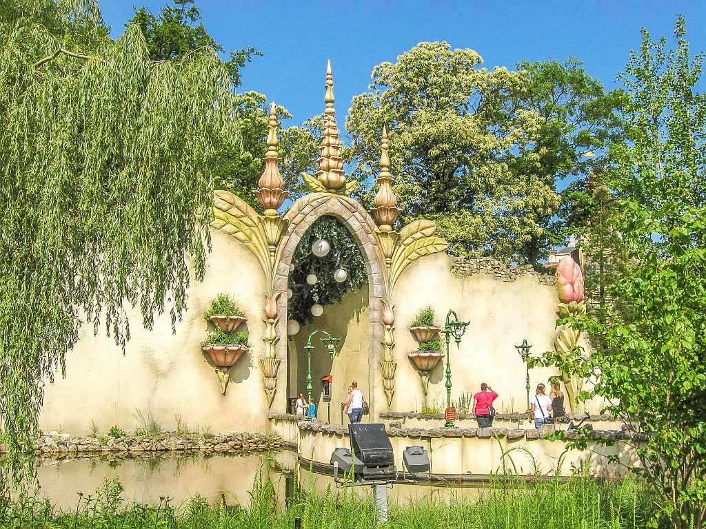 a fairy-tale like entrance into a wall with lots of trees and and surrounded by water, a few people getting into the entrance, the Efteling Amusement park in the Netherlands