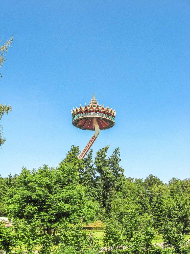 a pagoda type of a viewing platform that goes up in the air, surrounded by green trees
