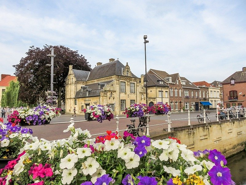 colorful flowers hanging in on a railing and a bridge along the water with some beautiful houses in Dutch style at the background, Valkenburg in the Netherlands