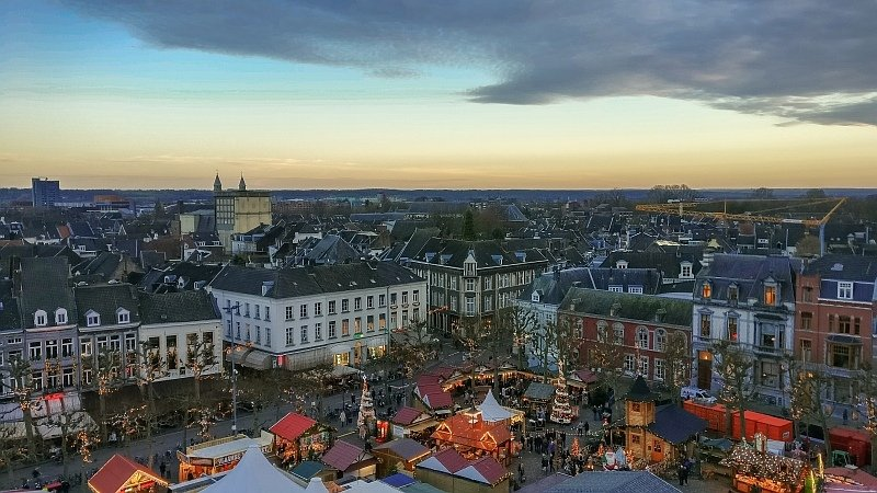 a view from above of a city at dusk with a Christmas market on a square and lots of lights and decorations, Vrijthof Square in Maastricht during Christmas market