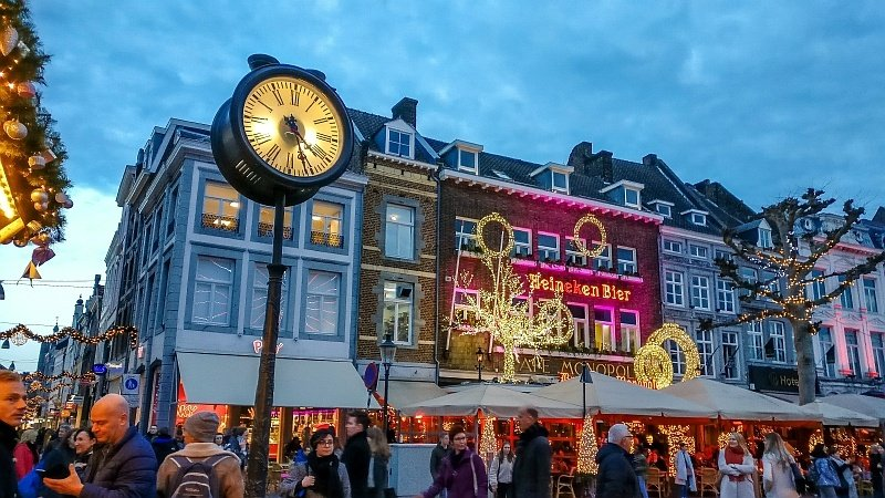 festively decorated buildings with lights and a round city clock on a pole