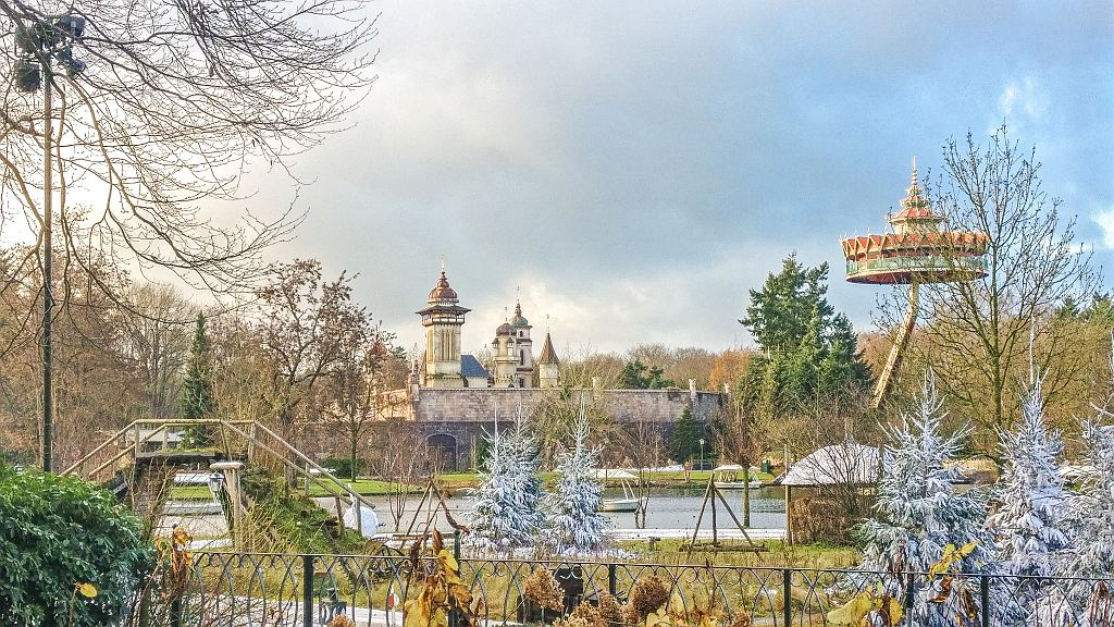 a fairy-tale like castle and a temple like observation tower and fir trees covered with artificial snow in the Efteling