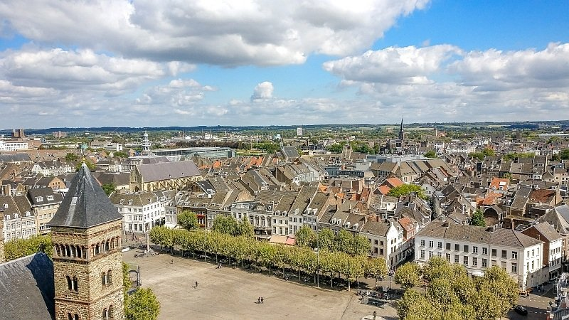 a bird's-eye view of a city with a square in the middle and a church tower at left frot corner, view from St Johns Church in Maastricht