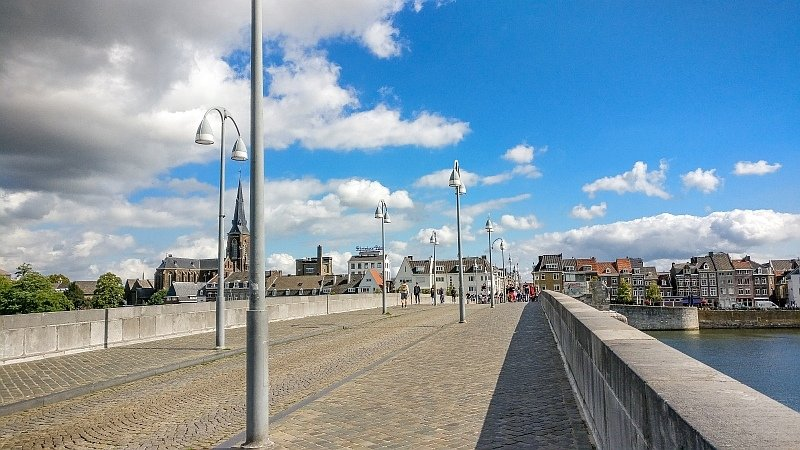 a view from walking on a bridge to a city skyline with a church and lamp poles on the bridge, the St Servatius bridge in Maastricht