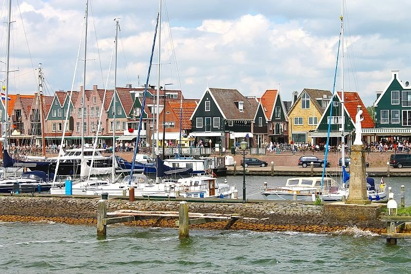 fisherman houses along water with some boats with masts on the foreground, Volendam, the Netherlands