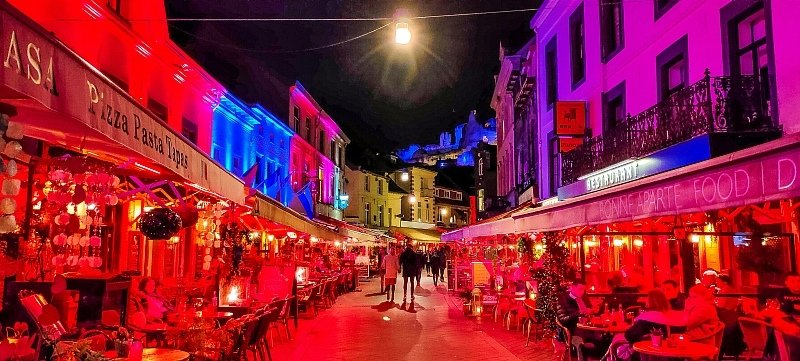 a street lined up with lots of restaurants and cafes lit up in different colors in the night and the end ruins of a castle on a top of a hill, Valkenburg