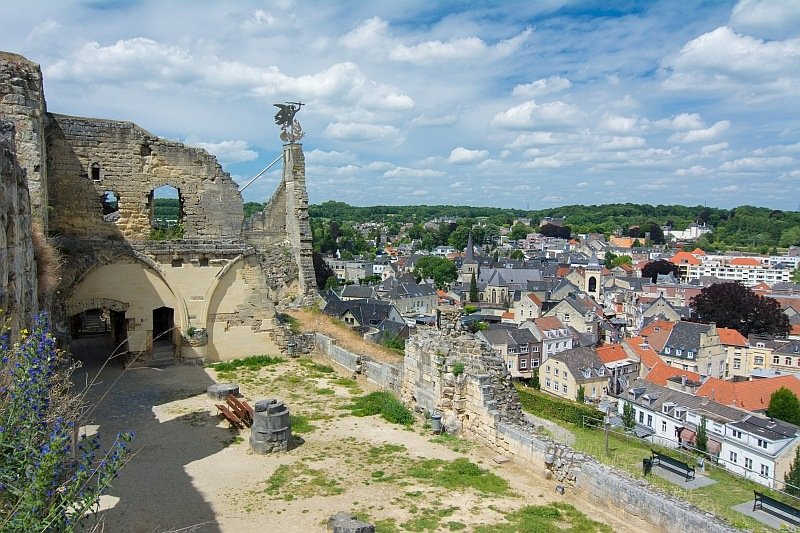 ruins of an old castle on top of a hill with a beautiful view to a small town and some green hills at the background, castle ruins in Valkenburg