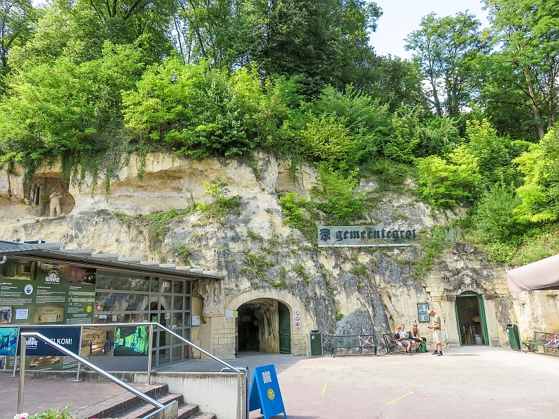 an entrance of a quarry under rocks covered with green trees, entrance to the Gemeentegrot in Valkenburg