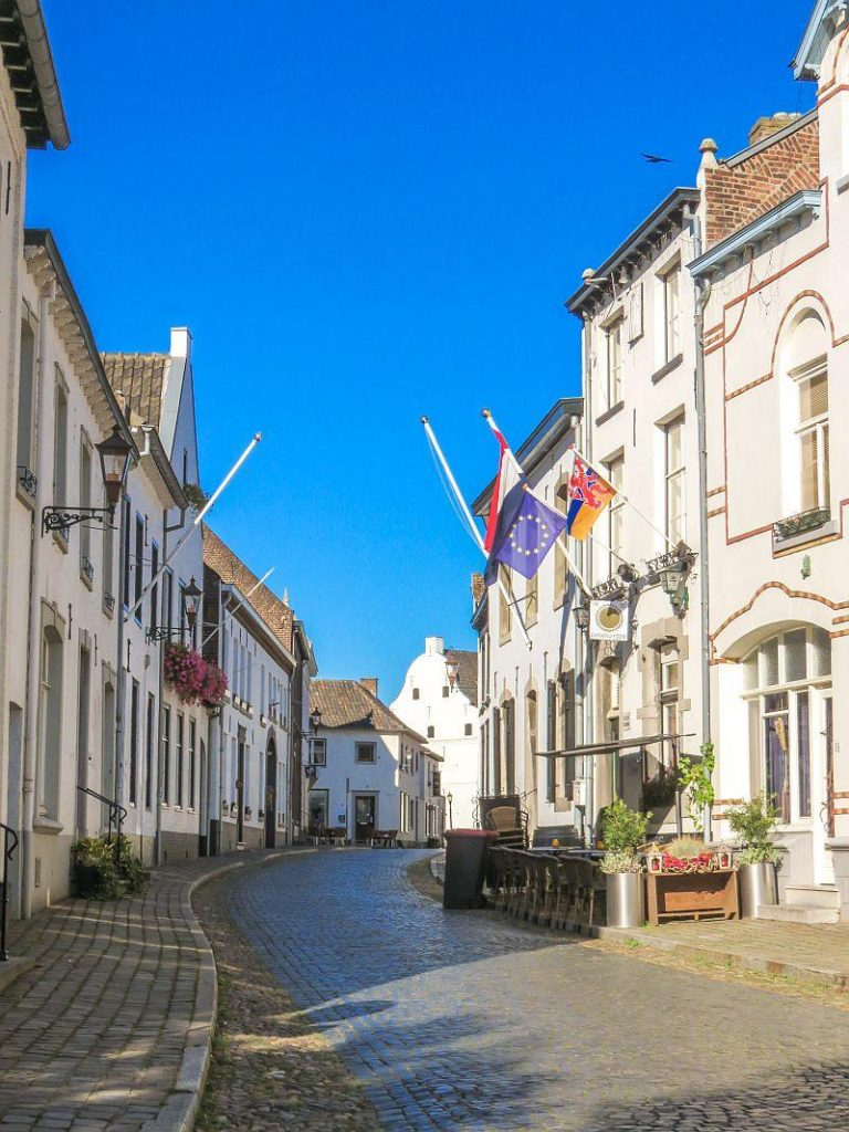 a cobblestone street lined up with white buildings with flag mast on some of them and flags blowing in the wind, on one side some tables and chairs on the sidewalk, part of a cafe, the little white town Thorn