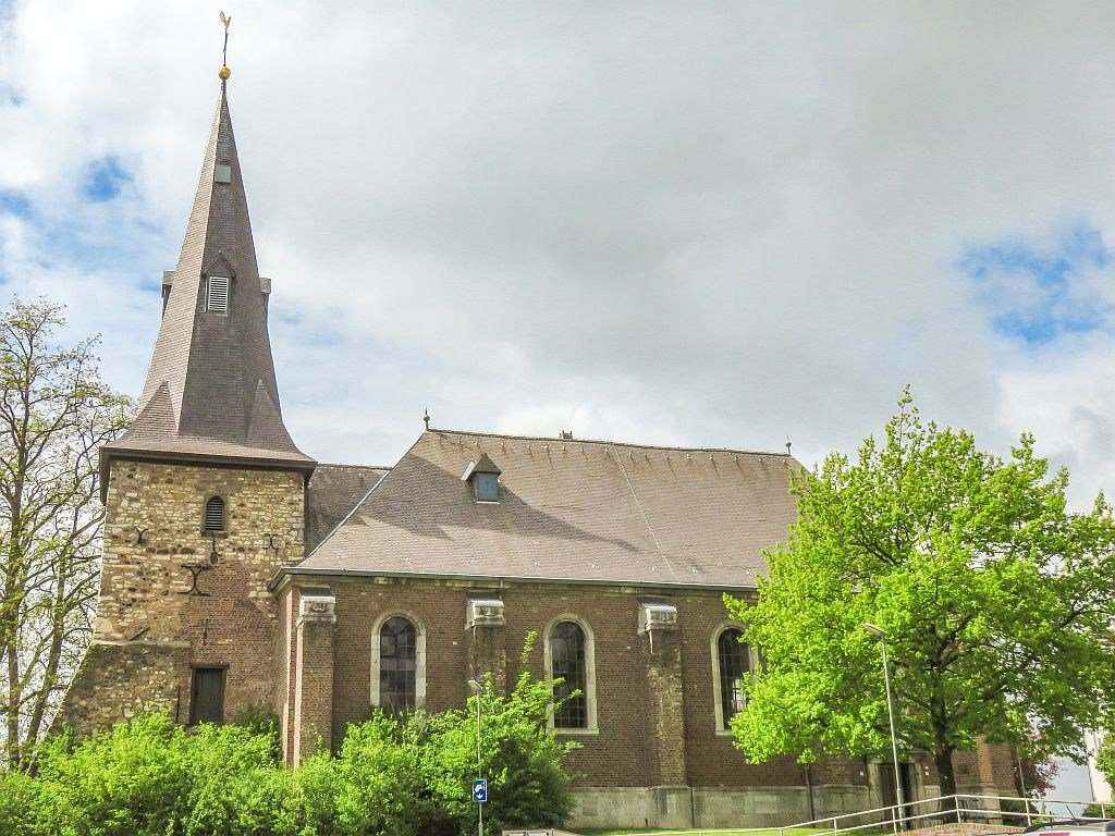 a brick church with an old church tower and some green trees in front, the Protestant Church in Vaals, the Netherlands