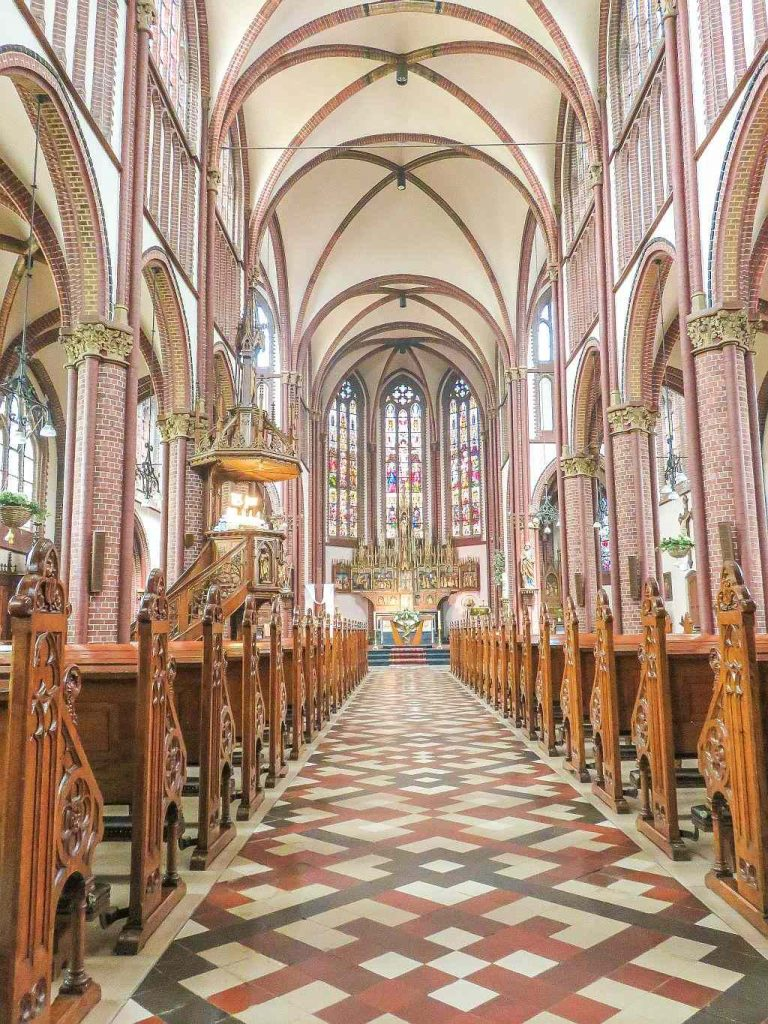 interior of a church with nice tile floor, arches and stained glass on the windows, Saint Paul's Church in Vaals