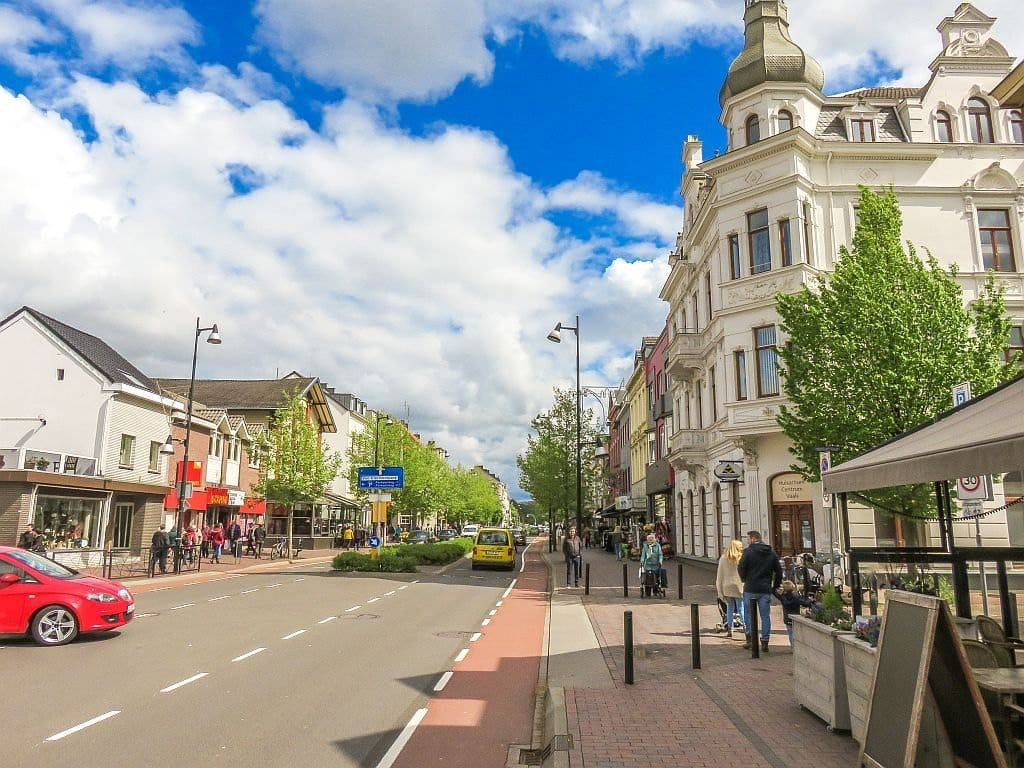 a busy two-way street divided by some green trees in the middle, main street in Vaals, Netherlands