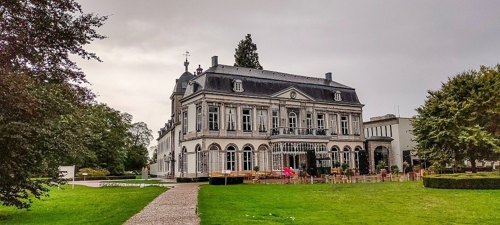 a large white building with a huge green loan in fron and grey sky, Vaerhartelt Castle Hotel in the Netherlands