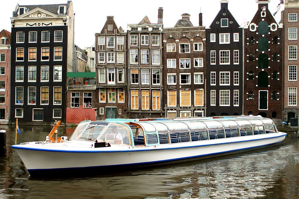 gingerbread type of houses in Amsterdam on a canal with a boat in front of them