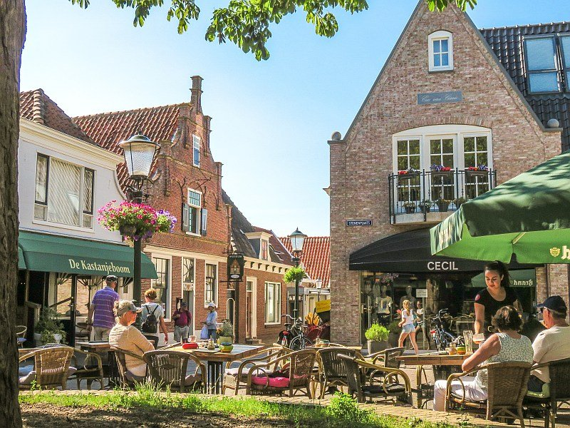 people sitting in a cafe on a a small square under trees, Den Burg on Texel