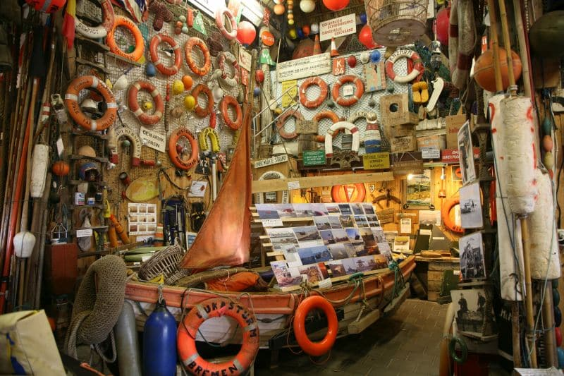 a room with walls covered with beachcombed things like life belts and other things connected with the ships and a boat in the middle of the room, Flora Beachcomber Museum on Texel