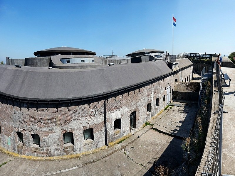 a large curved fort with small windows and the Dutch flag, UNESCO Fort Pampus, Netherlands
