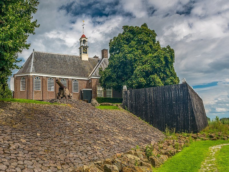a church on a dike and a canon in front. Schokland, Netherlands
