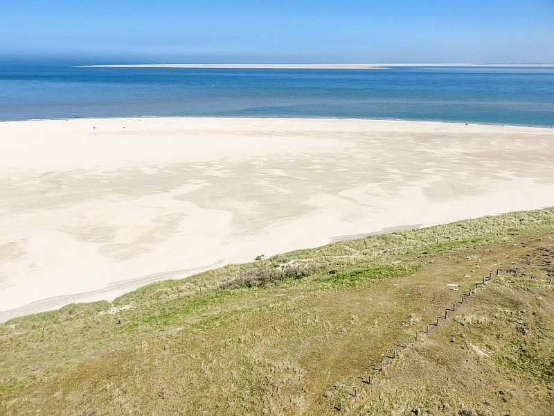 a view from a lighthouse to a white-sand beach and blue sea, view from the Texel lighthouse
