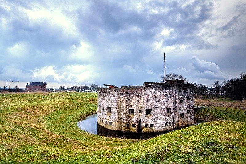 ruins of a fort surrounded by a moat and a castle far in the background, Westbatterij in Muiden