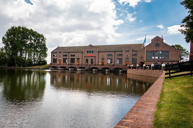 a large industrial type of a building with red bricks on the water, UNESCO Wouda pumping Station, Netherlands