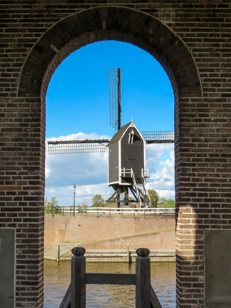 a framed view through an arch of a windmill against a blue sky with a few white fluffy clouds, Hesuden Visbank